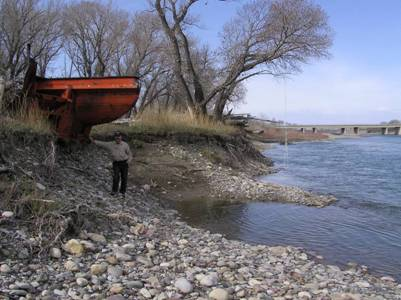 Photo of the south bank of the Oldman River immediately east of the Highway 2 bridge (shown in background) and west of Fort MacLeod. The photo shows a massive snow plough scoop wedged into the bank. The spring and seep habitat required by S. bertae is so small that such anthropogenic disturbances could completely destroy the habitat.